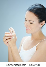 Woman putting cream on hands. Copy space
