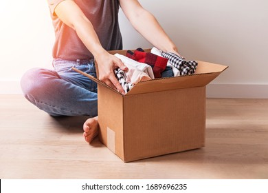 Woman putting different clothes in a carboad box. Clothes donation or reuse concept
