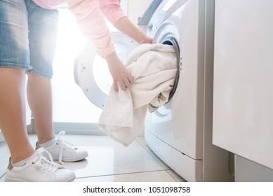Woman putting dirty laundry into washing machine