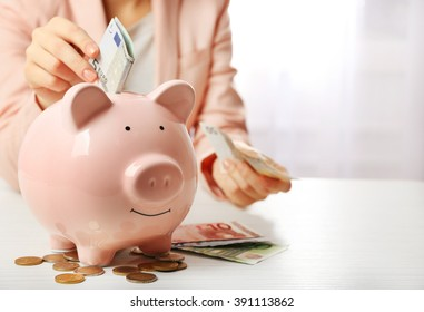 Woman putting euro banknote into a piggy bank on the table. Financial savings concept