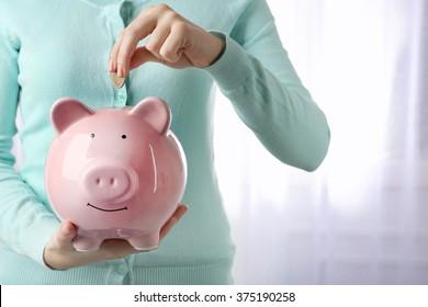 Woman putting euro coin into a piggy bank. Financial savings concept