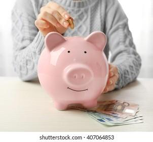 Woman putting euro coin into a piggy bank on the table. Financial savings concept