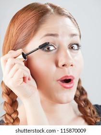 woman putting eyelash on her eyelids