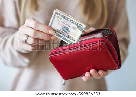 Woman is putting fifty dollars in the wallet