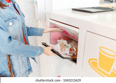 Woman putting garbage and leftovers of the fastfood restaurant to the recycling rubbish bin