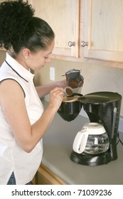 Woman putting grounds into filter in coffee machine