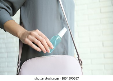 Woman putting hand sanitizer in purse indoors, closeup. Personal hygiene during COVID-19 pandemic
