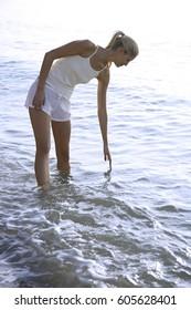 woman putting hand in water in ocean