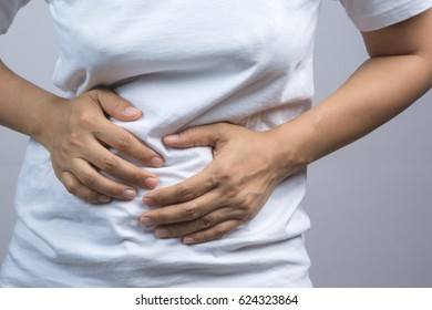 Woman putting her hands for belly or stomach ache on grey background