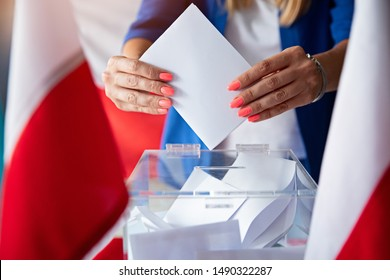 Woman putting her vote to ballot box. Poland political elections