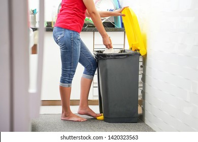Woman putting leftover food in black recycling bin in the kitchen