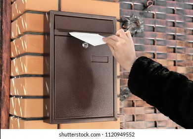 Woman putting letter in mailbox outdoors