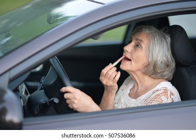 Woman putting lipstick in the car