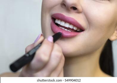 Woman putting makeup lipstick. Caucasian girl putting lip gloss pink lipstick smiling happy, close up.