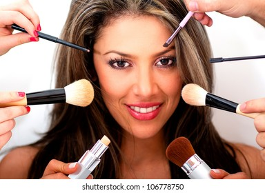 Woman putting makeup on by professional styling people