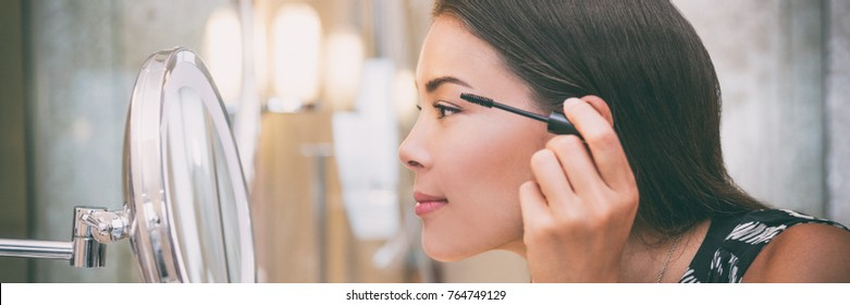 Woman putting mascara makeup in mirror banner getting ready for work doing morning makeup routine putting mascara in bathroom mirror at home. Beautiful Asian businesswoman applying eye make-up.