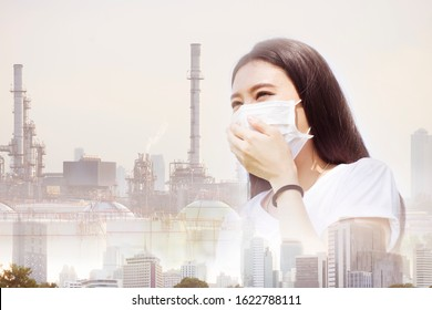 A woman is putting mask with protect bad pollution PM 2.5 from city and oil refinery at background.