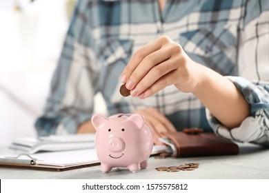 Woman putting money into piggy bank at table, closeup
