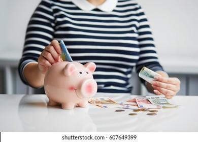 Woman putting money into small piggy bank