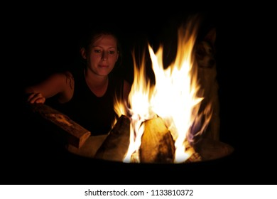 Woman putting more wood on the fire, camping and barbecue in the dark at night
