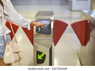 a woman is putting MRT coin for her traveling