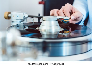 Woman putting needle on vinyl to play a record on turntable
