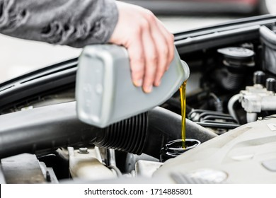 Woman putting oil into the engine of her car having opened the bonnet