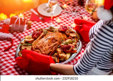 Woman putting on the Christmas decorated table turkey garnished with potato and garnet