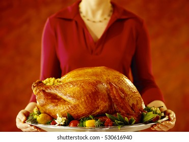 Woman putting on the Christmas decorated table turkey garnished
