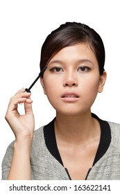 A woman putting on her mascara on the eyelashes