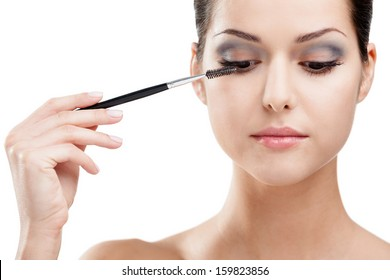 Woman putting on make up with cosmetic brush, isolated on white. Beauty procedures