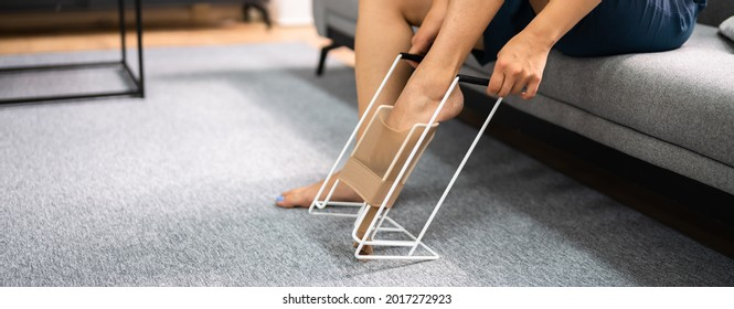 Woman Putting On Medical Compression Stockings Using Stocking Aid Puller