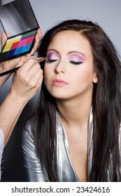 Woman putting on models eye make up