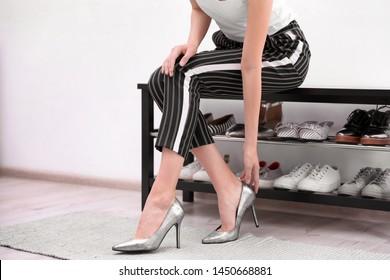 Woman putting on shoes indoors, closeup. Stylish hallway interior