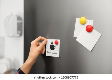Woman putting paper sheet on refrigerator door at home, closeup