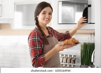 Woman putting plate with croissants in microwave indoors