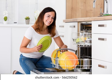 Woman Putting Plate In Dishwasher