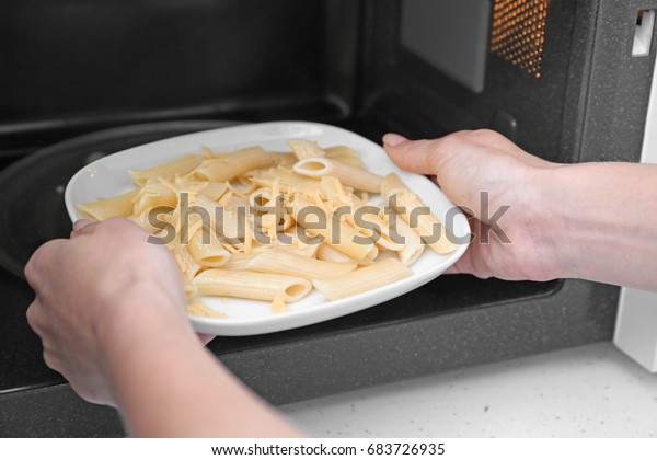 Woman putting plate of pasta with cheese into microwave oven in kitchen