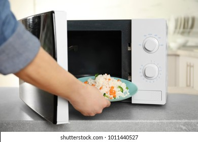 Woman putting plate of rice with vegetables in microwave oven, closeup