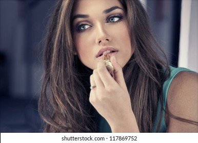 Woman putting red lipstick looking in mirror.
