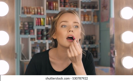 Woman putting red lipstick looking in mirror. Makeup at night getting ready before going to party.