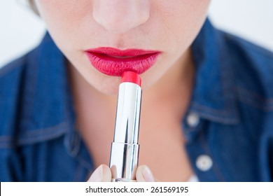 Woman putting red lipstick on white background