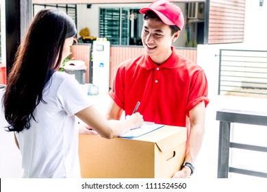 Woman putting signature in clipboard on cardboard box to receiving package with smiling delivery man in red uniform.courier service concept