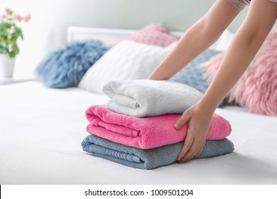 Woman putting stack of clean towels on bed
