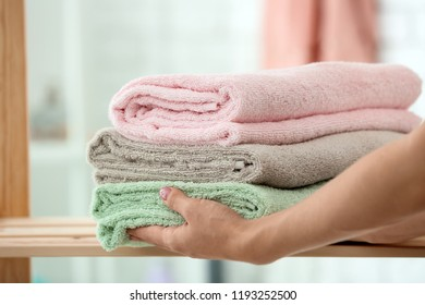 Woman putting stack of clean towels on shelf in bathroom