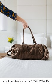Woman putting travel bag on bed in hotel room