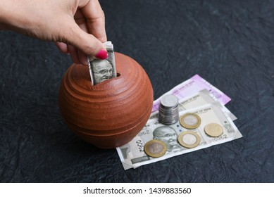 Woman putting wages in coin stack jar saving money for her child. Kids piggy bank for savings cash deposit for future. 500 rupee banknote India. Profit from business. New Indian currency notes of 2000