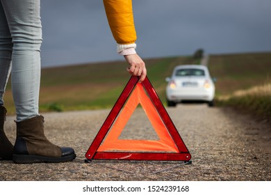 Woman putting warning triangle on road because car is broken. Safety red road warning sign before roadside assistent arrived.