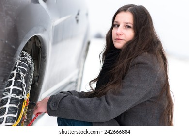 Woman putting winter tire chains on car wheel snow breakdown