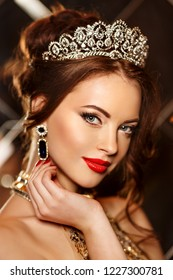 Woman queen princess in crown and lux dress, lights party background Luxury girl Long shiny healthy volume hair Waves Curls Updo Hairstyle. Salon Fashion model luxurious vintage interior Jewelry